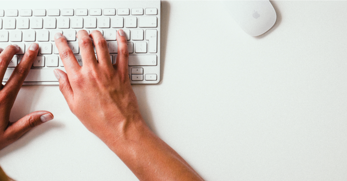 Hands typing at a computer keyboard.